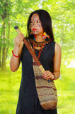 Amazonian exotic woman with facial paint and black dress, natural bag hanging across upper body, pulling out blowgun Stock Image