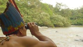 Amazonian Indigenous Man Watching Through A Binocular A Person In A Kayak. Amazonian Indigenous Warrior Watching Through A Binocular A Person In A Kayak In stock video footage