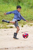 Amazonian Quechua boy playing soccer. Puyopungo, Ecuador - January 7, 2012 - A Quichua boy playing soccer in gum boots. The Quichua are the largest of the Royalty Free Stock Image