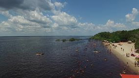 The Amazonians enjoying a hot and beautiful day on the beach in Amazon, Brazil stock footage