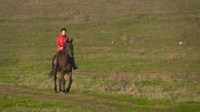 Amazzone che galoppa su un campo verde a cavallo Movimento lento stock footage