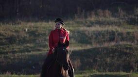 Amazzone che galoppa su un campo verde a cavallo Movimento lento video d archivio