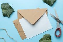 Ambachtenvelop en vorm voor tekst en groene bladeren op een heldere in lichtblauwe achtergrond Hoogste mening stock afbeeldingen