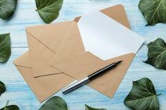 Ambachtenveloppen met een spatie voor tekst en groene bladeren op een blauwe houten lijst Hoogste mening stock afbeeldingen