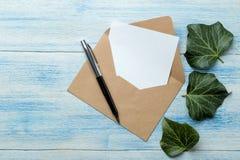 Ambachtenveloppen met een spatie voor tekst en groene bladeren op een blauwe houten lijst Hoogste mening stock foto