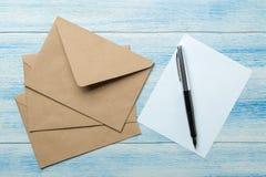 Ambachtenveloppen met spatie voor tekst op een blauwe houten lijst Hoogste mening stock fotografie