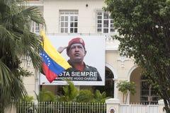Ambassad av Venezuela i havannacigarr med den Hugo Chavez affischen Fotografering för Bildbyråer