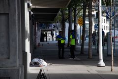 Ambassadeurs de Van de binnenstad van Seattle op stoep naast de dakloze mens stock afbeelding