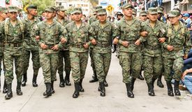 Ambato, Ecuador / Feb 15, 2015 - Army soldiers clear road by walking arm in arm. Ahead of Carnaval parade royalty free stock photos