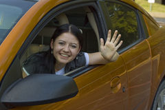 Amber 0185. Young woman waving and smiling from her car Stock Image