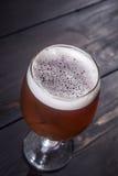 Amber ale on dark wood Stock Image