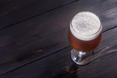 Amber ale on dark wood Royalty Free Stock Photos