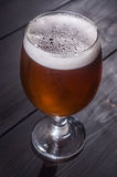 Amber ale on dark wood Royalty Free Stock Images