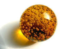 Amber ball. With bubbles on white background under the bright sun Stock Image