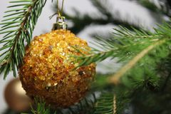 Amber ball on the Christmas tree on a white background. gemstone amber shimmers in the light. orange light. Christmas decorations. Amber ball on the Christmas royalty free stock image