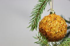 Amber ball on the Christmas tree on a white background. gemstone amber shimmers in the light. orange light. Christmas decorations. Amber ball on the Christmas stock photo