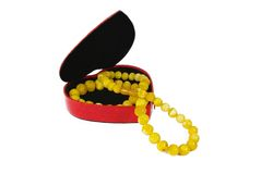 Amber beads in gift box on white background. Amber beads in heart form gift box on white background Stock Photography