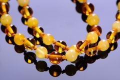 Amber beads accessory on blue background Royalty Free Stock Photo