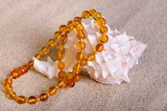 Amber beads on sea beach background Royalty Free Stock Images