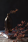 Amber bottle vase of dried berry sticks on book table centerpiec Royalty Free Stock Images