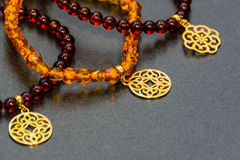 Amber bracelets with gold pendants. Royalty Free Stock Photos