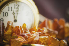 Amber and a clock in a background Stock Images