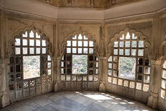 Amber Fort Beauty. Beautifully architectured balcony inside Amber Fort overlooking the lush green Aravalli hill range in Jaipur, Rajasthan. The artwork showcases Royalty Free Stock Image