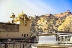 Amber Fort con la luce dorata del sole e la montagna verde come fondo, Ragiastan, India Immagine Stock Libera da Diritti