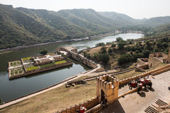 Amber Fort Gardens. View of the Maota lake and beautifully decorated Amber Fort gardens in Jaipur, Rajasthan. The lush green Aravalli hill range and elephants in Royalty Free Stock Photo