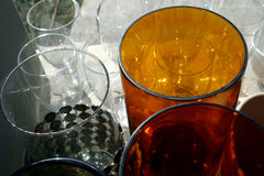 Amber Glass. An amber glass sits on a table outside with other glassware royalty free stock photo