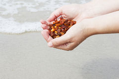 Amber in the hand with a bright reflection on the palm against the background of the sea. Bright glow of the sun stone in female hand. Mineral from resin Royalty Free Stock Photo
