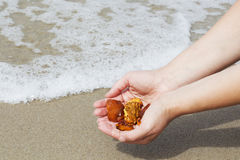 Amber in the hand with a bright reflection on the palm against the background of the sea. Bright glow of the sun stone in female hand. Mineral from resin Stock Image