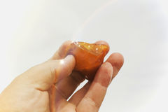 Amber in the hand with a bright reflection on the palm against the background of the sea. Bright glow of the sun stone in female hand. Mineral from resin Stock Photography