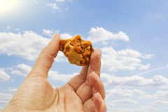 Amber in the hand with a bright reflection on the palm against the background of the sea. Bright glow of the sun stone in female hand. Mineral from resin Royalty Free Stock Photos