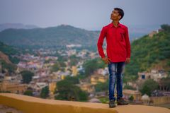 Amber, India - September 19, 2017: Close up of an unidentified Indian man wearing a red t-shirt a jean pants with city. Behid in the city of Amber, India Royalty Free Stock Photos