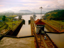 Ship Enters Panama Canal at Sunrise. Waiting for the locks to open and close as we travel the Panama Canal. The morning sun reflects off the heavy mist making Stock Photography
