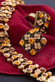 Amber Necklet. With rings as closeup on red satin Royalty Free Stock Photos