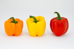 Amber, red and yellow pepper. Isolated on white Stock Image