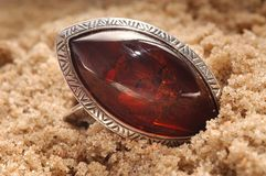 Amber ring in sand. An amber ring in sand, Close up Royalty Free Stock Photo