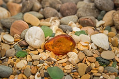 Amber stone. Mineral amber. Rosin yellow amber. Sunstone on a beach of pebbles. Royalty Free Stock Photos