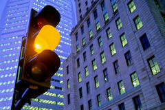 Amber traffic light in city. Closeup of amber traffic light in city at night with skyscraper background Stock Photos