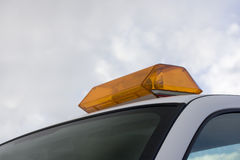 Amber warning revolving lights on a roof of servic. Amber warning revolving lights (lightbar) on a roof of service vehicle against sky Royalty Free Stock Images