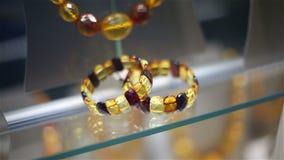 Amberparels en armbanden op een show-venster van winkel van juwelen stock video