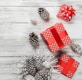 Ambiance de Noël sur la table de cuisine, les cadeaux décoratifs de sapin et les cônes Image stock