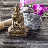 Ambiance for feng shui and detox treatment. Spa beauty treatment concept - symbol of exfoliation for inner beauty with Buddha on old wood, gray stones and pink Royalty Free Stock Photo