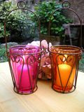 Ambiance lantern candles outdo. Ambiance candles ablaze with warm  up-close colors of pink and yellow good   home decor concept shot  alight in a lantern holder Stock Photography