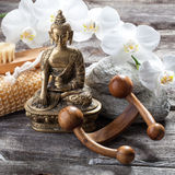 Ambiance for massage and purity cure with Buddha in mind. Spa beauty treatment concept - symbol of massage and peeling for inner beauty with Buddha on old wood Royalty Free Stock Image
