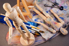 Ambience of art workplace. Classic wooden dummy and other art tools Royalty Free Stock Images