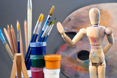 Ambience of art workplace. Classic wooden dummy and other art tools Stock Photos