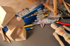 Ambience of art workplace. Multiple art tools and classic wooden dummy on a gray background Royalty Free Stock Image